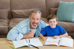 Father helping his son with homework in living room Stock Photo