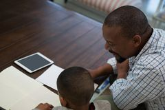 Father helping his son with homework in living room. At home Stock Photos