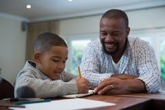 Father helping his son with homework in living room. At home Stock Photography