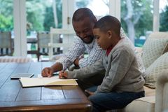 Father helping his son with homework in living room. At home Stock Image