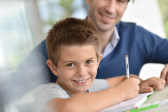 Father helping his son with homework. Man helping son with homework Stock Images