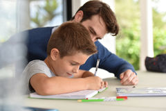 Father helping his son with homework. Man helping son with homework royalty free stock images