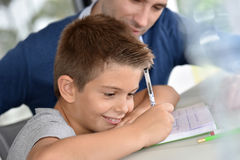 Father helping his son with homework. Man helping son with homework Stock Photography