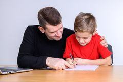 Father helping his son with homework. At table Royalty Free Stock Photography