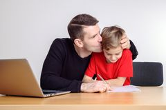 Father helping his son with homework. At table Royalty Free Stock Images