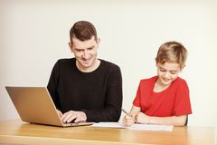 Father helping his son with homework. At table Stock Image