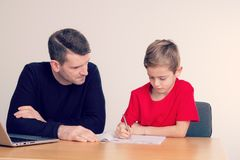 Father helping his son with homework. At table Royalty Free Stock Photo