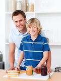 Father helping his son prepare the breakfast Royalty Free Stock Photography