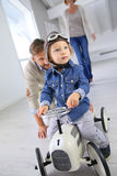 Father helping his son riding retro toy car. Man helping little boy on a retro toy car Stock Photos