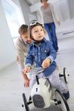 Father helping his son riding retro toy car Stock Photos