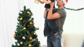 Father helping his son to decorate the Christmas tree stock video