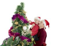 Father helping his son to decorate Christmas tree. Young father helping his son to decorate a Christmas tree in the studio, isolated on white background Stock Images