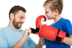 Father helping his son to put on boxer gloves isolated on white Stock Photo