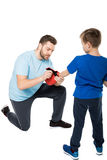 Father helping his son to put on boxer gloves isolated on white Stock Images
