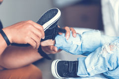 Father is helping his son to tie his shoes in the room on bed. Royalty Free Stock Images