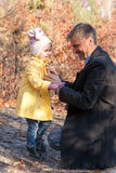Father Helping Little Baby Daughter to Wear Coat Stock Photos