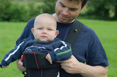 Father helping son into baby carrier. Sling Royalty Free Stock Images