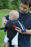Father helping son into baby carrier. Sling Stock Photo