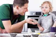 Father helping son baking muffins. Young father helping little son baking muffins Royalty Free Stock Images