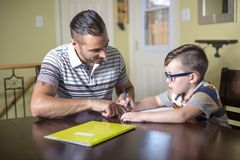 Father helping son do homework. Parent helps his child Stock Photo