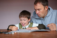 Father helping son doing homework Stock Photos
