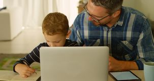 Father helping son with his homework 4k. Father helping son with his homework at home 4k stock video