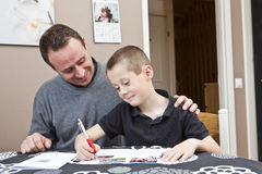Father helping son with homework Stock Photo