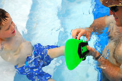 Father helping son in pool. Father helping son put on swim fin in pool stock images