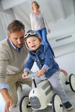 Father helping son riding car toy Stock Photography