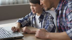 Father helping son to do homework on laptop, education with modern technologies. Stock footage stock video footage