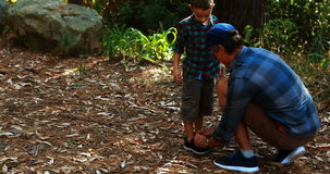 Father helping son to tie his shoe lace in the park. On a sunny day stock footage
