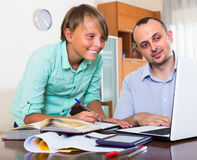 Father helping teenage son with homework Stock Photography