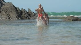 Father helps boy jump in azure sea water near old cliffs stock video