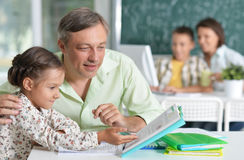 Father helps daughter with homework Stock Photos