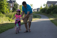 Father helps daughter ride her bicycle Royalty Free Stock Images