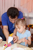 Father helps his daughter to make paper crafts Royalty Free Stock Photos