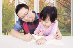 Father helps his daughter to study Stock Image