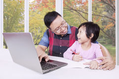 Father helps his female kid learning at home Stock Photo