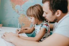 Father helps his little daughter to write at the desk in the room with the map on the wall stock photos