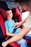 Father helps his son to fasten belt on car seat while his son is Stock Photo