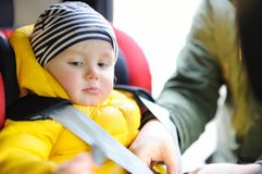 Father helps his toddler son to fasten belt on car seat royalty free stock photography