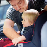 Father helps his toddler son to fasten belt on car seat Royalty Free Stock Images