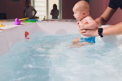 A father helps is infant boy during swimming lessons in the pool.