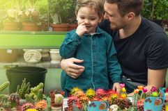 Father and her baby boy in a plant shop looking at cacti. Gardening In Greenhouse. Botanical garden, flower farming royalty free stock photography