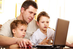 Father with her children using laptop Stock Photos