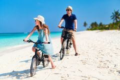 Father and daughter riding bikes at tropical beach Stock Photo