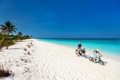 Father and daughter riding bikes at tropical beach Stock Image