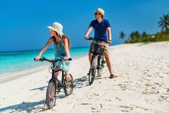 Father and daughter riding bikes at tropical beach. Father and her little daughter riding bikes at tropical beach having fun together Royalty Free Stock Photography