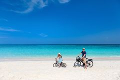 Father and daughter riding bikes at tropical beach. Father and her little daughter riding bikes at tropical beach having fun together royalty free stock image