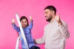 Father and her little daughter with thumbs up over pink background. Adult man and baby girl are happy. Father and her little daughter with thumbs up over pink Stock Photos